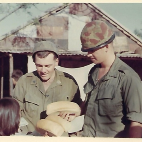 Kids selling bread to Corpsman and Lt Andrews